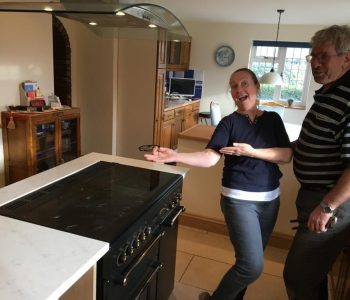 Couple showing off new kitchen island with built-in oven