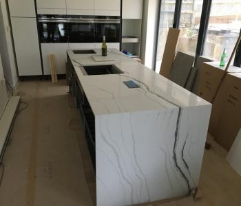 Classic quartz 'Monaco' kitchen island with view of garden